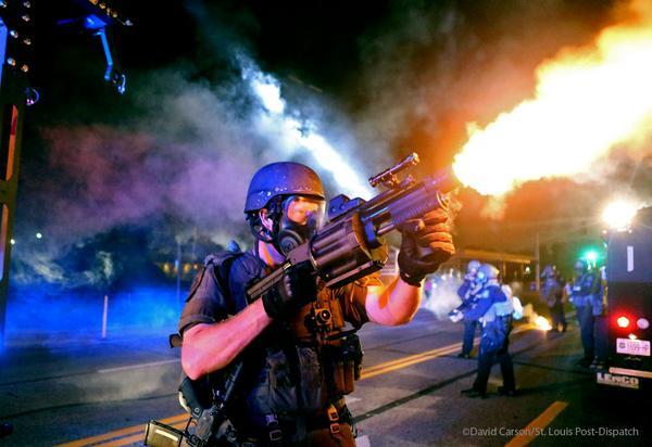 Un policier lançant des grenades lacrymogènes