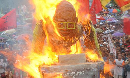 Les manifestants brûlent une effigie du président des Philippines.