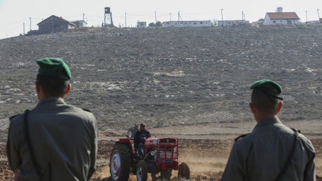 Un paysan palestinien de Qusra travaillant la terre, à l'arrière plan, la colonie sioniste d'Esh Kodesh