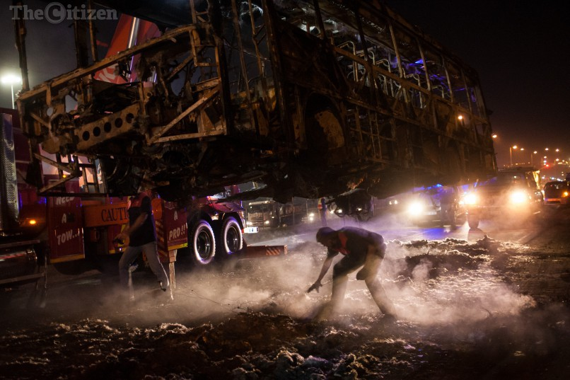 Les pompiers enlèvent la carcasse d'un bus incendié par les émeutiers à Hammanskraal
