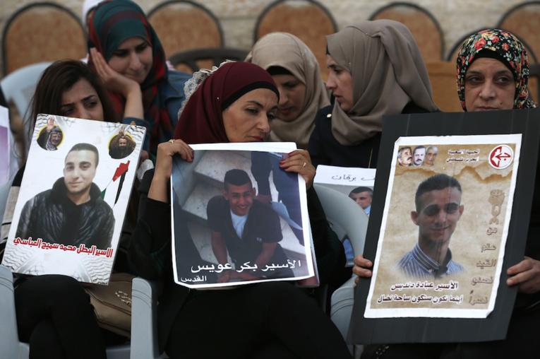 Des Palestiniennes brandissent des photos de leurs proches emprisonnés en Israël, devant les bureaux de la Croix rouge de Jérusalem Est, avant-hier 25 mai