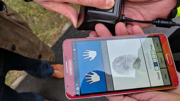 Un scanner d'empreinte portatif relié à un smartphone.