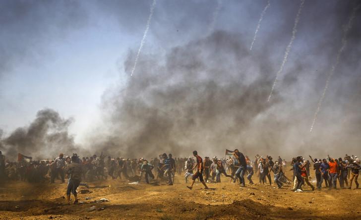 Des manifestants palestiniens se protègent des gaz lacrymogènes israéliens pendant une manifestation à Jabalia, au centre de la bande de Gaza, hier 8 juin