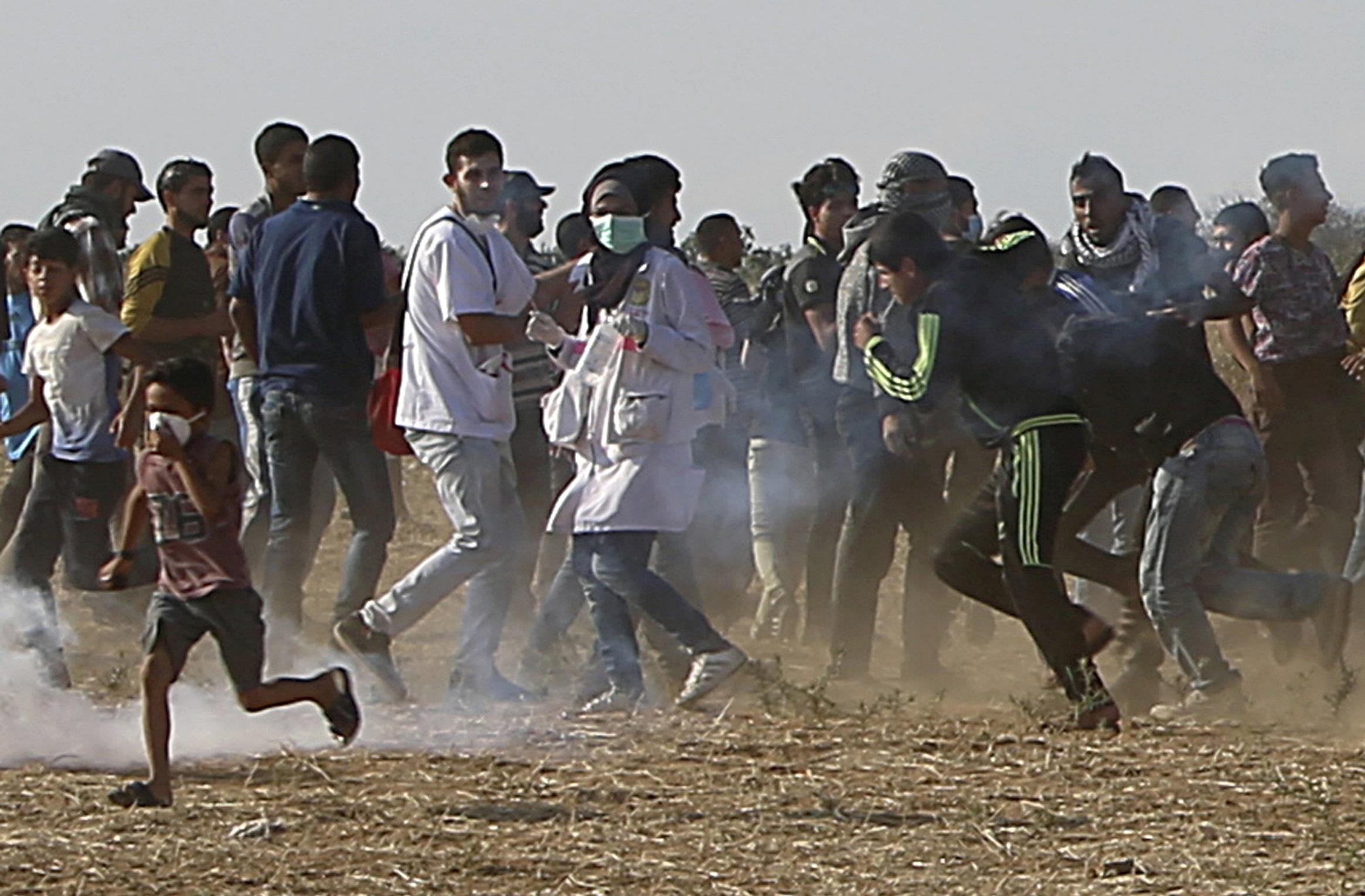 Razan Najjar, au centre de l'imgae, alors qu'elle courrait avec des manifestants pour se protéger des gaz lacrymogènes tirés par la troupe israélienne près de la frontière de la bande de Gaza, peu de temps avant qu'elle soit abattue.