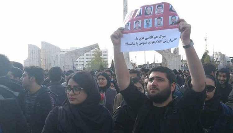 Un manifestant de l'Université Awad brandit les portraits de ses 10 condisciples tués dans l'accident