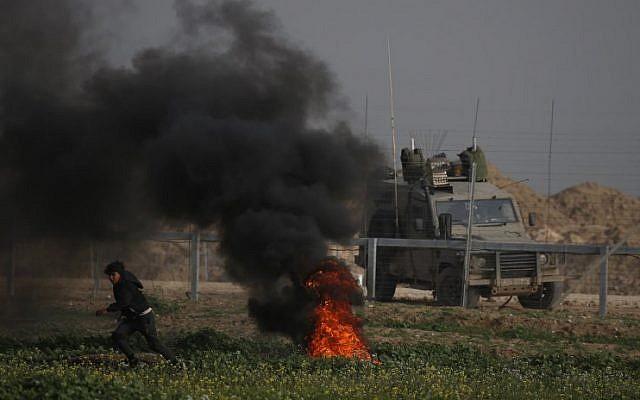 Manifestants palestiniens et blindé israélien de part et d'autre de la clôture hier vendredi