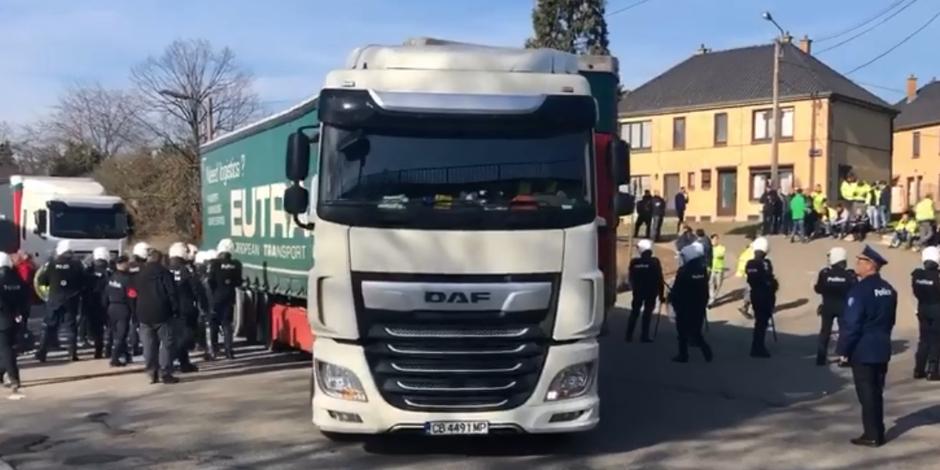 Les camions entrent dans le site sous la protection de la police
