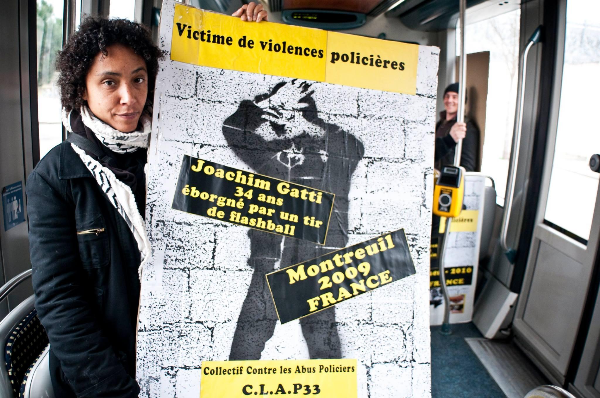 Militante du CLAP portant une pancarte contre les violences policières