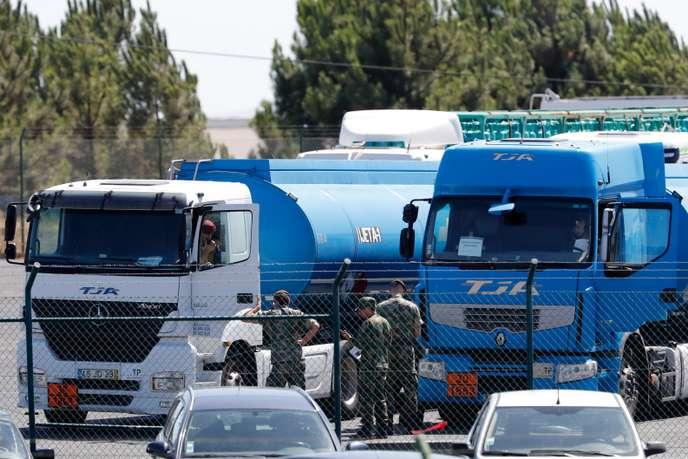 Des soldats surveillent le ravitaillement des transporteurs d'essence, à Aveiras