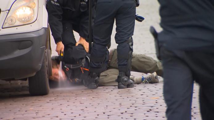 Un manifestant maintenu au sol et gazé en pleine face