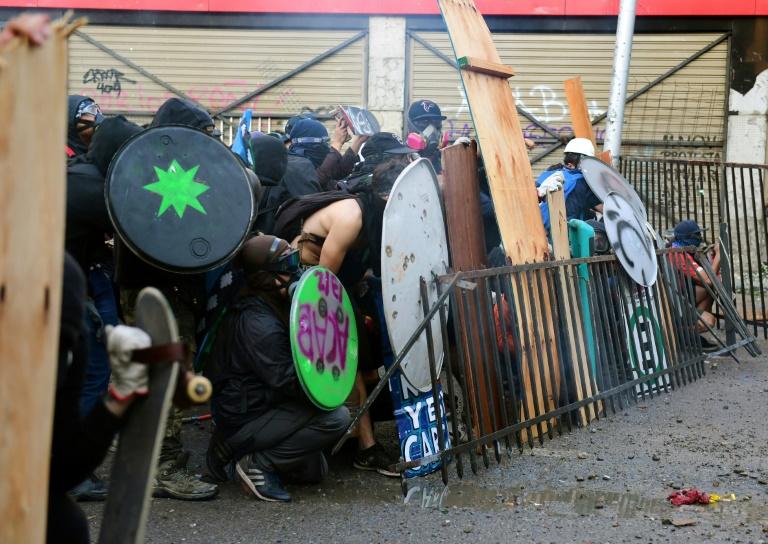 Des manifestants se protègent face aux forces de l'ordre à Santiago, hier vendredi