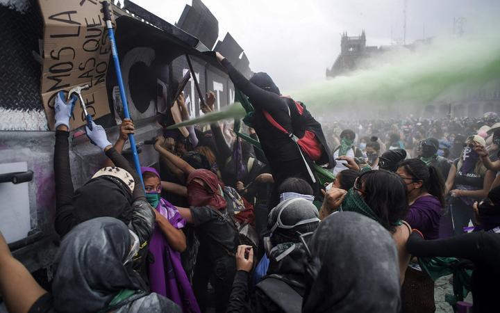 Les manifestantes essayent de pénétrer dans le palais national à Mexico à l'occasion du 8 mars 2021