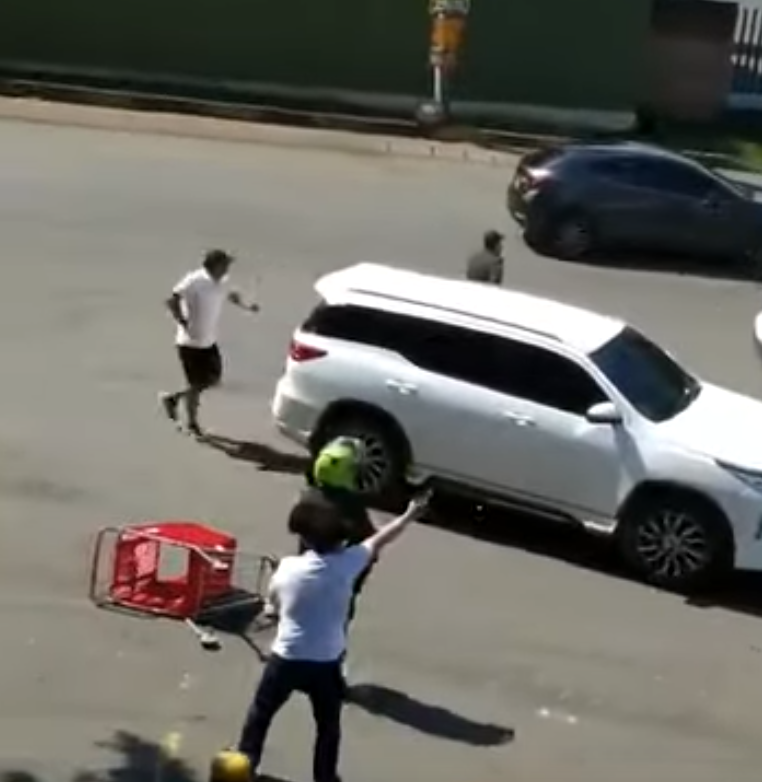 Un milicien ouvrant le feu sur les manifestants à coté d'un policier en uniforme
